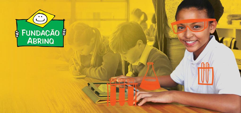 Una niña sentada en el pupitre junto a sus compañeros de clase con dibujos fantasiosos de gafas, vasos y viales de laboratorio. Esta imagen tiene el logotipo de la Fundacáo Abrinq.