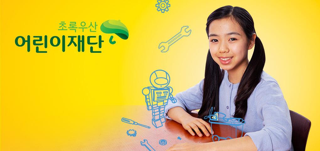 Una niña sentada en un pupitre de la escuela con dibujos fantasiosos de un robot y herramientas. Esta imagen tiene el logotipo de Green Umbrella Children's Foundation.